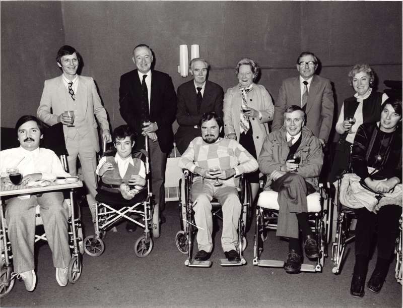 Five residents in wheelchairs with their escorts, holding glasses of wine at an awards event