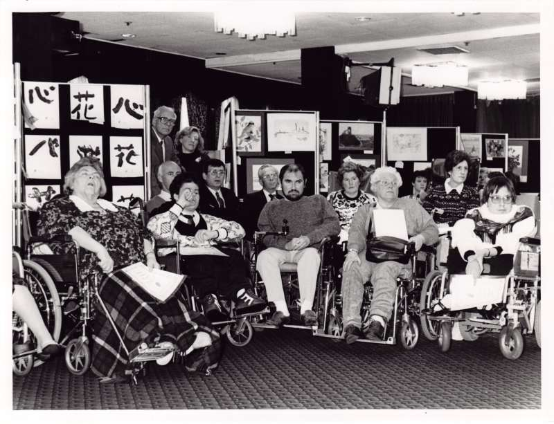 Group photograph of residents in wheelchairs holding various award certificates