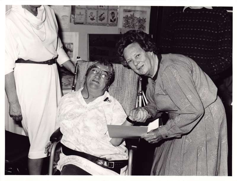Lady in a wheelchair being presented with an award by another lady who is also holding her hand
