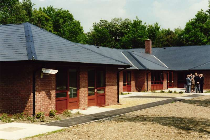 Colour photo of the outside of a single storey brick building with wooden doors leading to rooms for residents