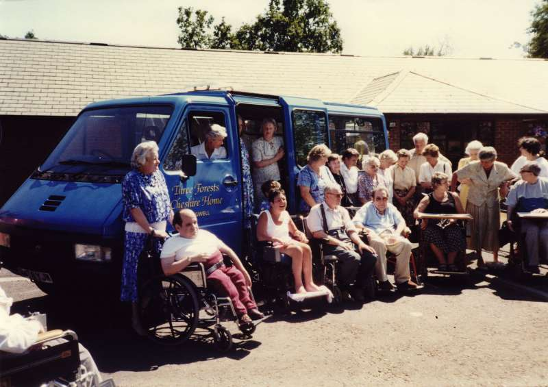 Group of many people, some in wheelchairs, standing in front of a blue minibus