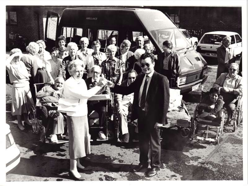 Lady handing over keys of a minibus to a man, with a group of people watching on, minibus in background