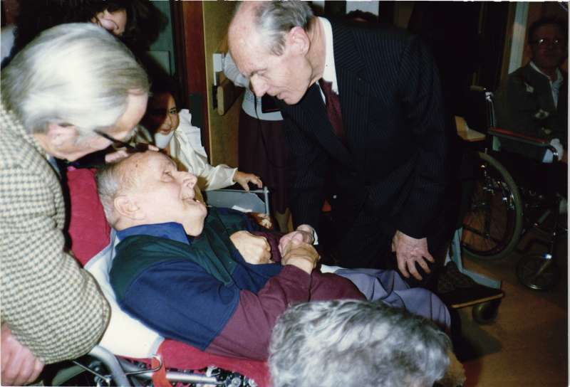 Leonard Cheshire talking and shaking hands with a man in a wheelchair, with others watching on