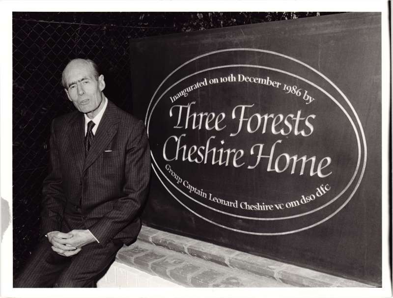 Leonard Cheshire in a suit sat next to the Three Forests Cheshire Home sign