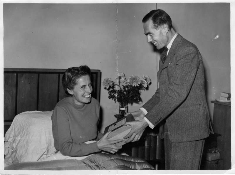 A smiling woman sat in bed receives a boxed parcel from Leonard Cheshire