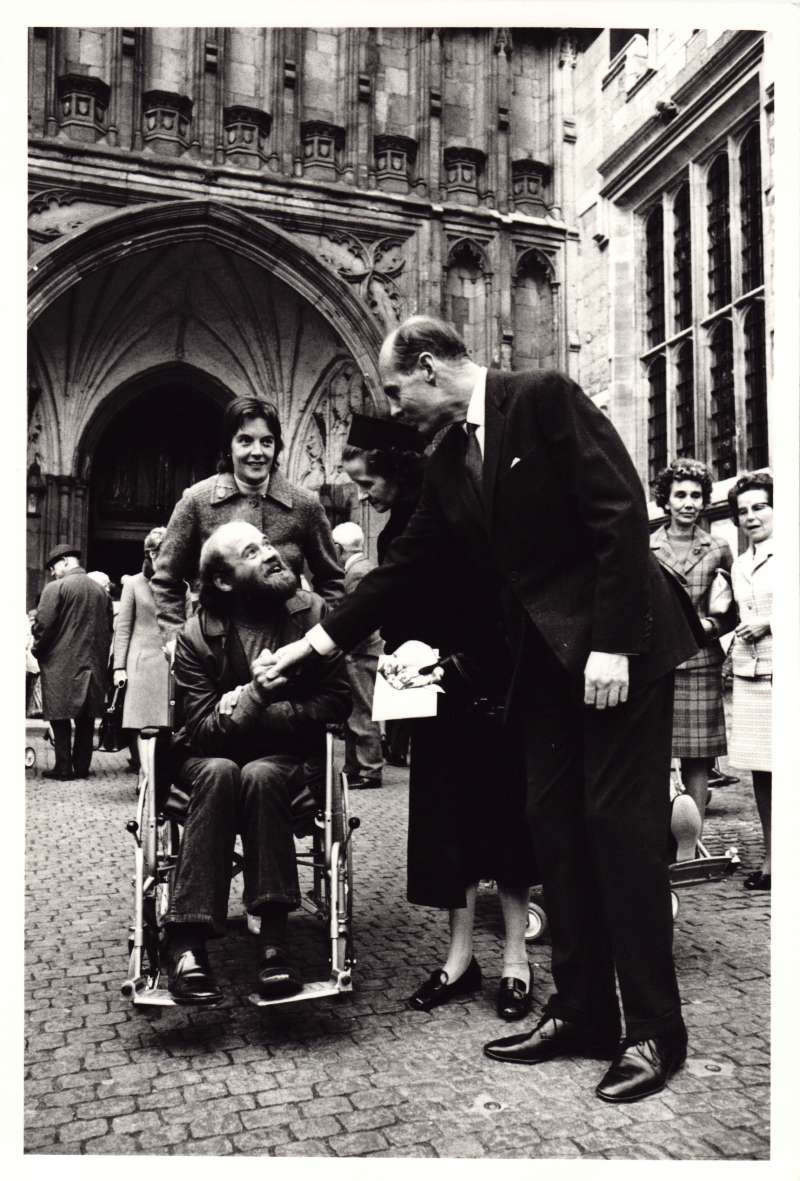 Leonard Cheshire and Sue Ryder shaking hands and talking with a man in a wheelchair outside Westminster Abbey