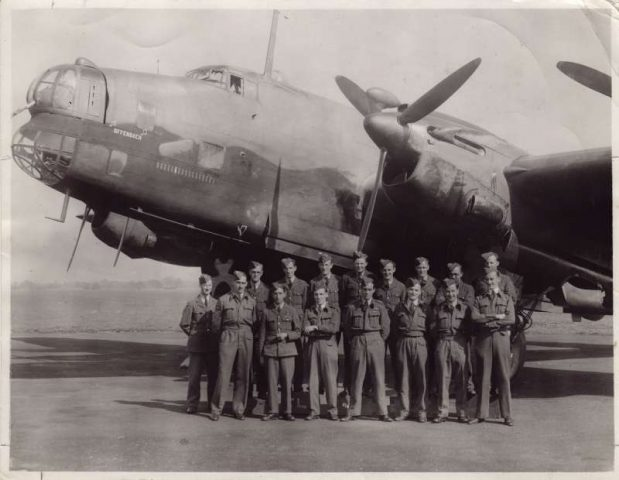 Squadron of airmen from WWII stood in front of a Lancaster plane