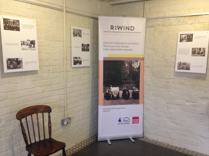 A photograph of the exhibition at Sharpe's Pottery Museum, showing a banner and panels on the walls