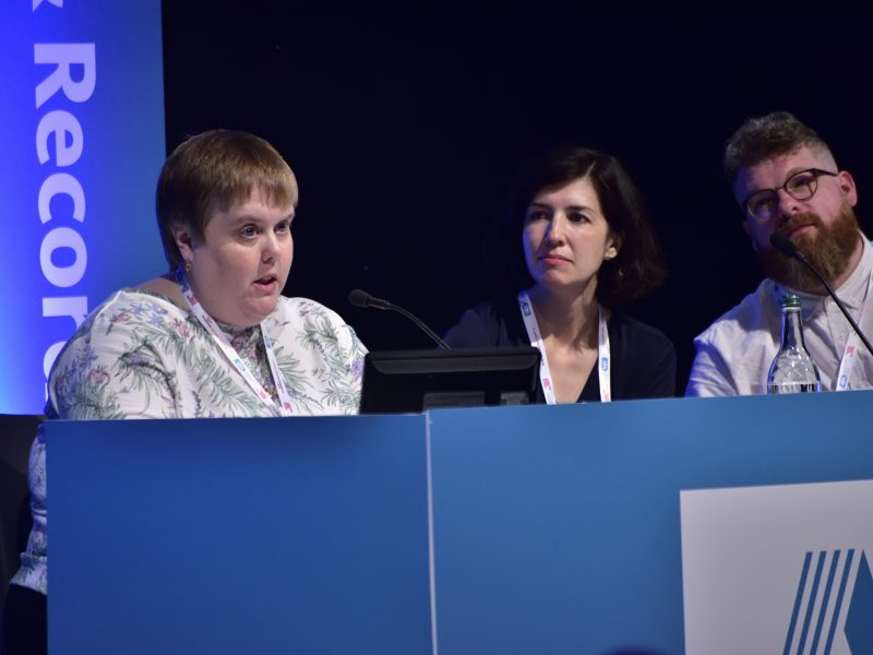 A woman in white sits and talks into a microphone, sat at a panel table while three others watch
