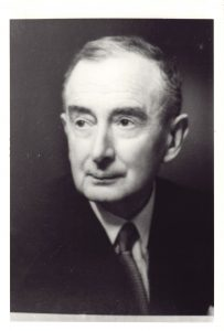 A portrait photograph of a man in a shirt, jacket and tie