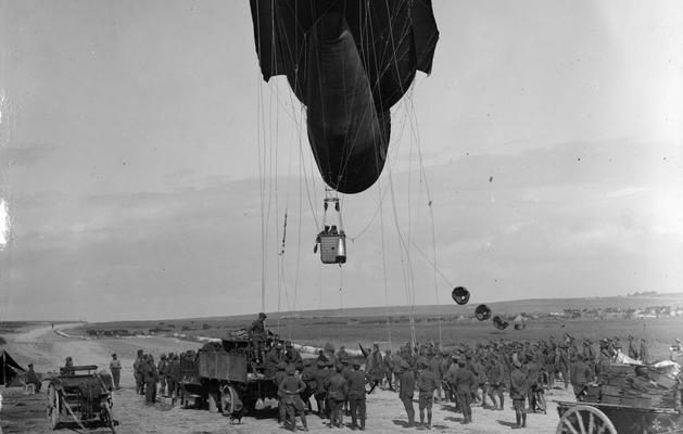 A kite balloon ascending above a group of men and vehicles on the ground