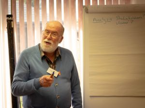 A man holding a pen stood in front of a flip chart