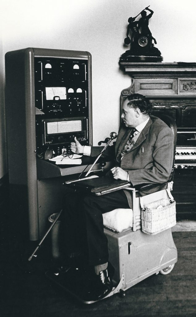A man operating a radio unit in front of an ornate fireplace