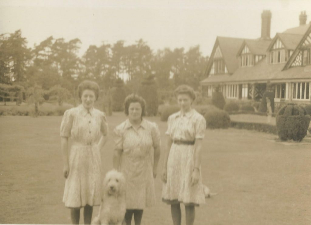 three WAAF waitresses and Simon the poodle in grounds of Petwood hotel, Woodhall Spa