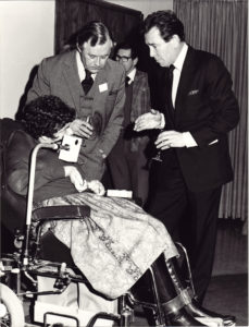 A woman in a mouth operated wheelchair talking to two dignitaries