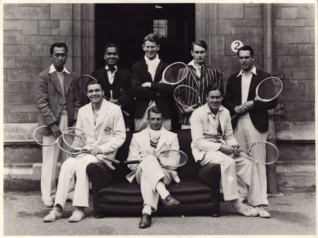 A group of young man in tennis clothing sat on a sofa outside a brick building
