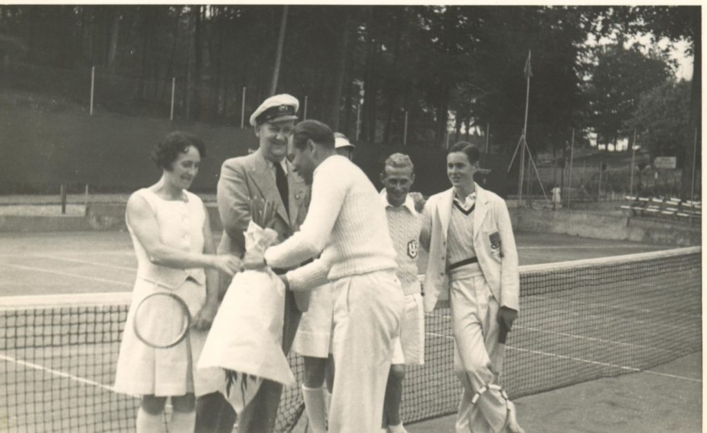 A man dressed in tennis whites shakes hands over a tennis court net whilst others, including a man wearing a naval officer's hat look on smiling