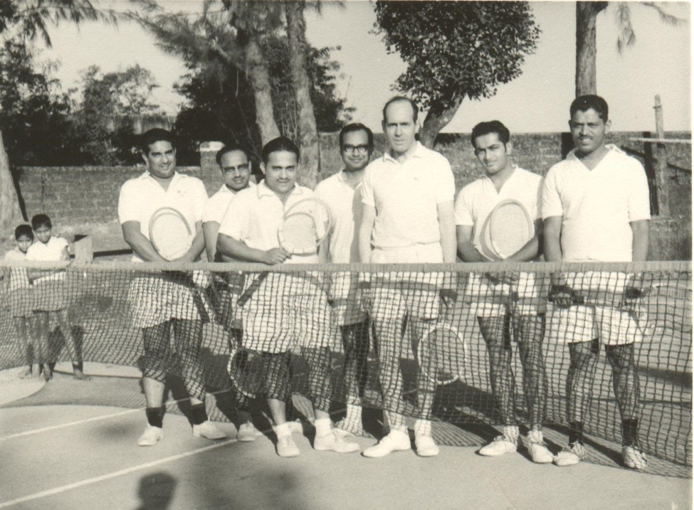 A man stood at a net on a tennis court surrounded by other men in tennis whites